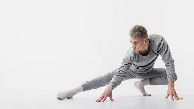 Vista frontal do dançarino masculino em agasalho e meias posando enquanto dança