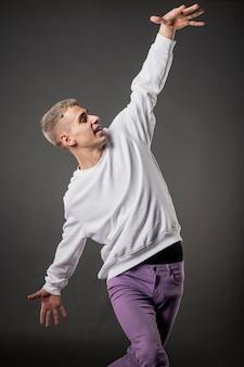 Vista frontal do dançarino masculino em jeans roxos dançando