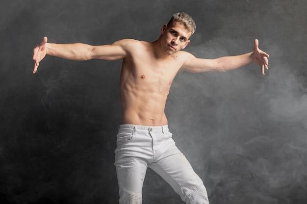 Vista frontal do dançarino masculino posando de jeans com fumaça