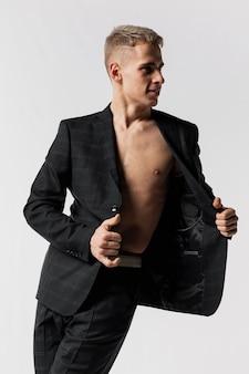 Vista frontal do dançarino no terno posando com blazer aberto