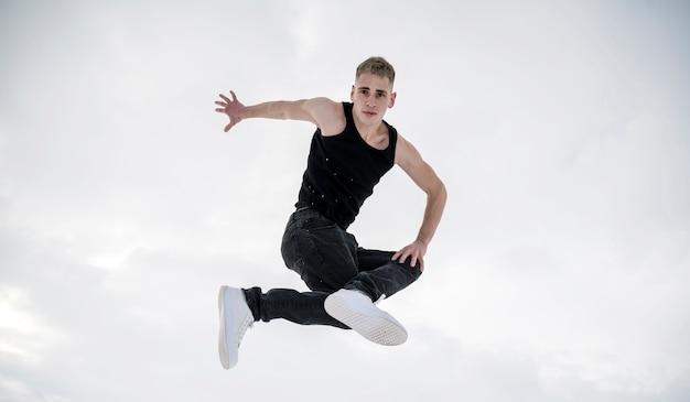 Vista frontal do dançarino posando enquanto no ar