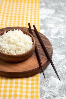 Vista frontal do delicioso arroz cozido dentro de um prato marrom na mesa branca