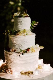 Vista frontal do delicioso bolo de casamento cremoso, decorado com eucalipto e rosas brancas em cima da mesa à noite