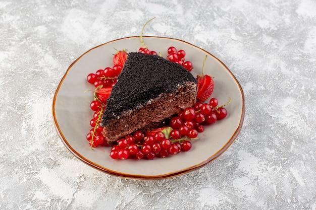 Vista frontal do delicioso bolo de chocolate fatiado com creme de chocolate e cranberries vermelhos frescos