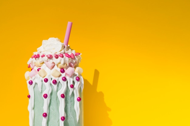 Vista frontal do delicioso milk-shake com fundo amarelo