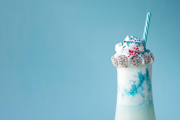 Vista frontal do delicioso milk-shake em fundo azul