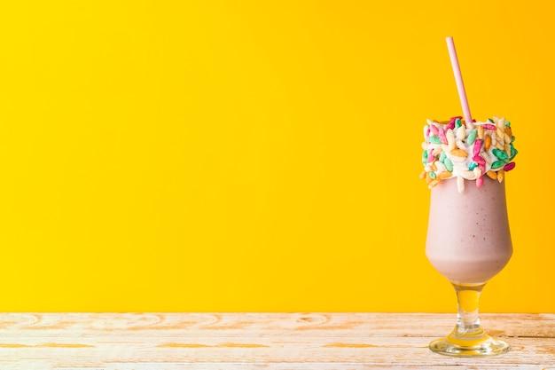 Vista frontal do delicioso milkshake em fundo amarelo