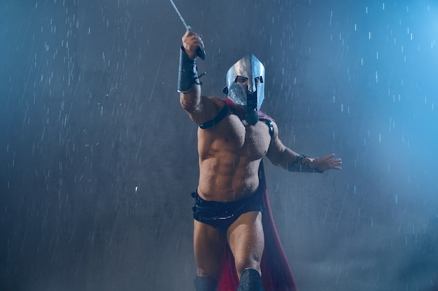Vista frontal do destemido gladiador romano molhado em capacete de ferro, atacando com espada. muscular, gritando, espartano sem camisa, com manto vermelho e armadura correndo durante a luta em tempo chuvoso.