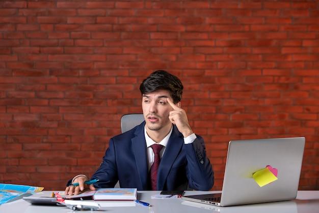 Vista frontal do empresário bonito estressado sentado atrás de seu local de trabalho com o laptop de terno plano de trabalho empreiteiro ocupação construtor trabalho empresarial projeto corporativo