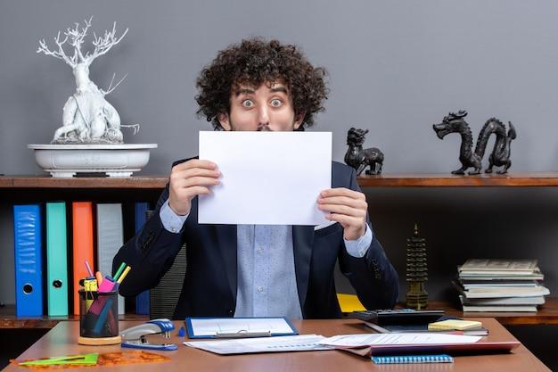 Vista frontal do empresário chocado segurando papéis na frente do rosto no escritório