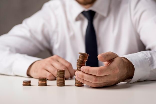 Vista frontal do empresário com moedas