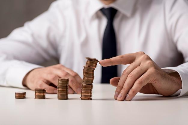 Vista frontal do empresário de terno e gravata com moedas