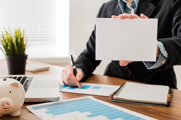 Vista frontal do empresário no escritório segurando um papel em branco