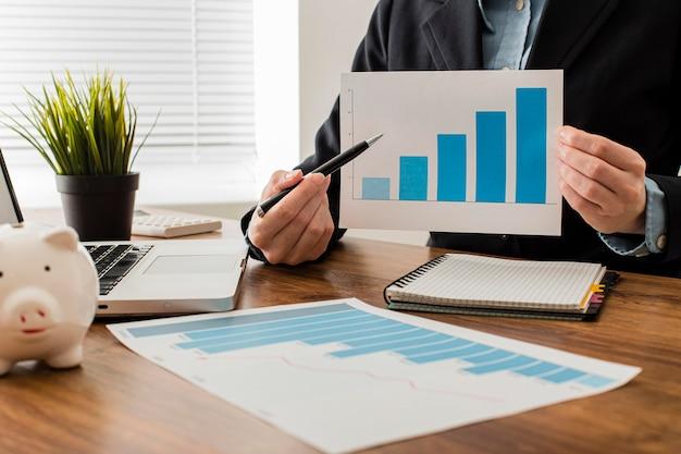 Vista frontal do empresário segurando um gráfico de crescimento