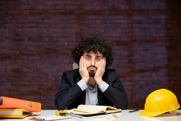 Vista frontal do engenheiro estressado sentado atrás de seu local de trabalho no plano de terno empreiteiro trabalho corporativo ocupação trabalho construtor projeto empresarial