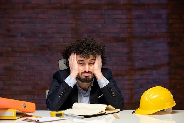 Vista frontal do engenheiro estressado sentado atrás do local de trabalho em terno empreiteiro construtor plano de ocupação de trabalho projeto de trabalho de negócios corporativos