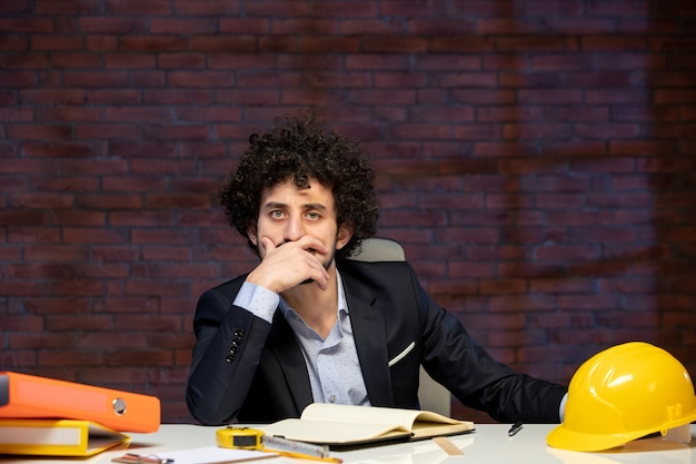 Vista frontal do engenheiro estressado sentado atrás do local de trabalho em um terno com capacete amarelo construtor de plano de negócios empreiteiro ocupação trabalho trabalho de projeto corporativo