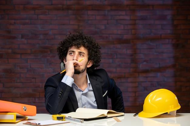 Vista frontal do engenheiro estressado sentado atrás do local de trabalho no plano de terno construtor de negócios trabalho ocupação empreiteiro projeto trabalho corporativo