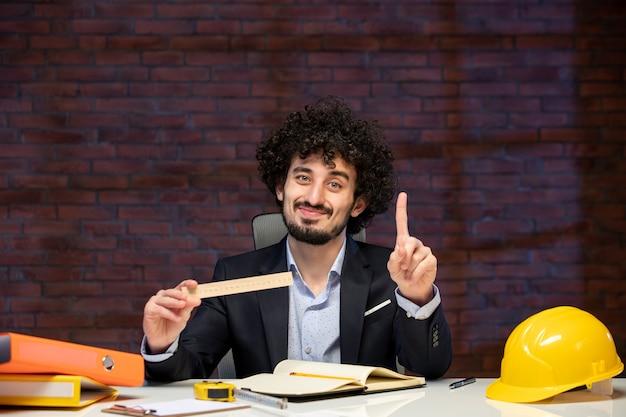 Vista frontal do engenheiro sentado atrás de seu local de trabalho em terno segurando régua plano empreiteiro trabalho ocupação construtor projeto trabalho corporativo