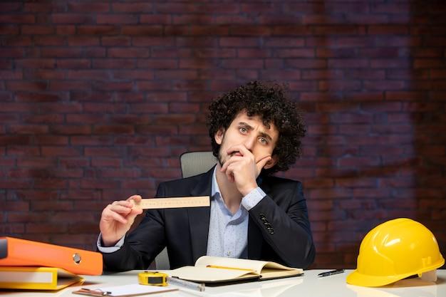 Vista frontal do engenheiro sentado atrás de seu local de trabalho em terno segurando régua plano empreiteiro trabalho ocupação corporativa construtor projeto trabalho
