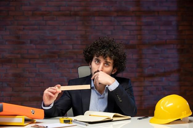 Vista frontal do engenheiro sentado atrás de seu local de trabalho em terno segurando régua plano empreiteiro trabalho ocupação corporativa construtor trabalho de negócios