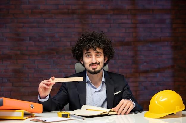 Vista frontal do engenheiro sentado atrás de seu local de trabalho em terno segurando régua plano empreiteiro trabalho ocupação corporativa construtor trabalho projeto de negócios