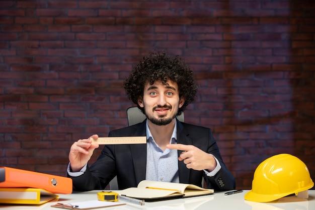 Vista frontal do engenheiro sentado atrás de seu local de trabalho em terno segurando régua plano empreiteiro trabalho ocupação corporativa trabalho projeto de negócios