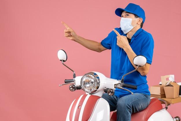 Vista frontal do entregador chocado com máscara médica e chapéu, sentado na scooter, apontando para cima no fundo cor de pêssego