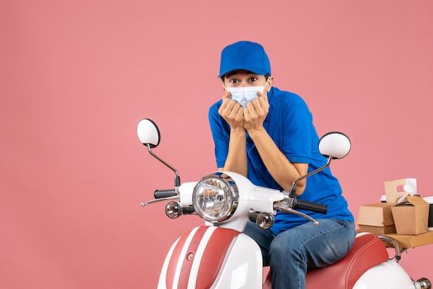 Vista frontal do entregador confuso com máscara médica usando chapéu, sentado na scooter sobre fundo cor de pêssego