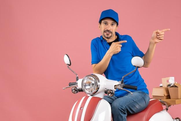 Vista frontal do entregador de chapéu, sentado na scooter, apontando para trás sobre um fundo de pêssego pastel