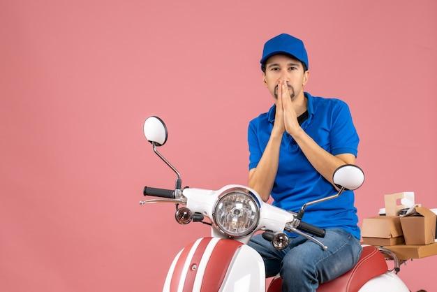 Vista frontal do entregador de chapéu, sentado na scooter, pensando profundamente no fundo cor de pêssego.