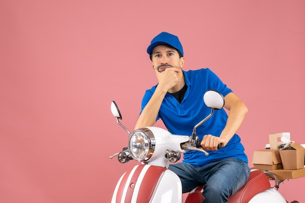 Vista frontal do entregador de chapéu, sentado na scooter, pensando profundamente no fundo de pêssego pastel