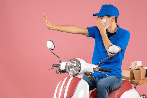 Vista frontal do entregador nervoso com máscara médica usando chapéu, sentado na scooter, fazendo gesto de parada sobre fundo de pêssego pastel