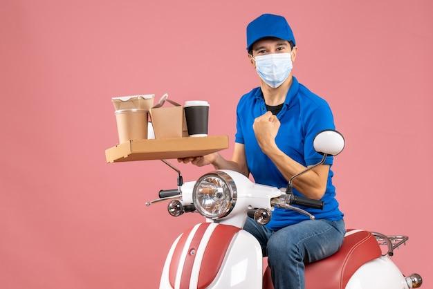 Vista frontal do entregador orgulhoso e ambicioso, mascarado, usando um chapéu, sentado na scooter, entregando pedidos em um fundo de pêssego