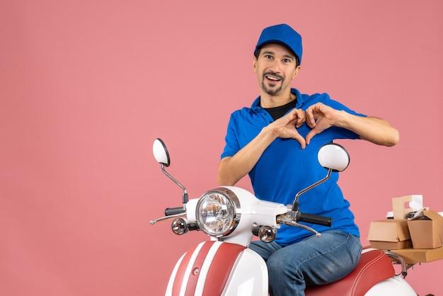 Vista frontal do entregador romântico usando chapéu, sentado na scooter, fazendo um gesto de coração em um fundo de pêssego pastel