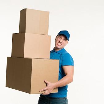 Vista frontal do entregador segurando caixas de papelão pesadas nas mãos