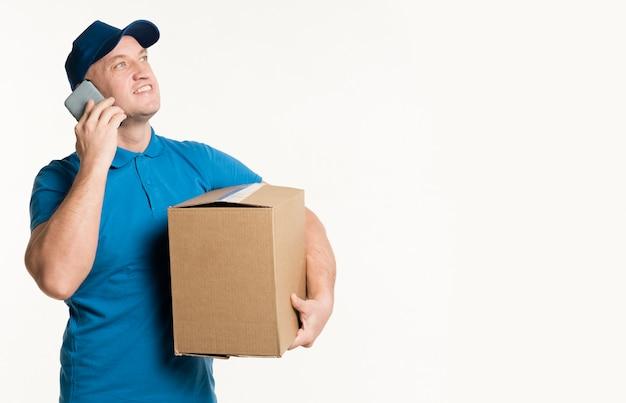 Vista frontal do entregador segurando o telefone e caixa de papelão