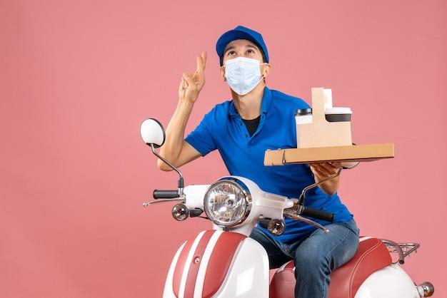 Vista frontal do entregador sonhador com máscara e chapéu, sentado na scooter, entregando pedidos em fundo cor de pêssego.
