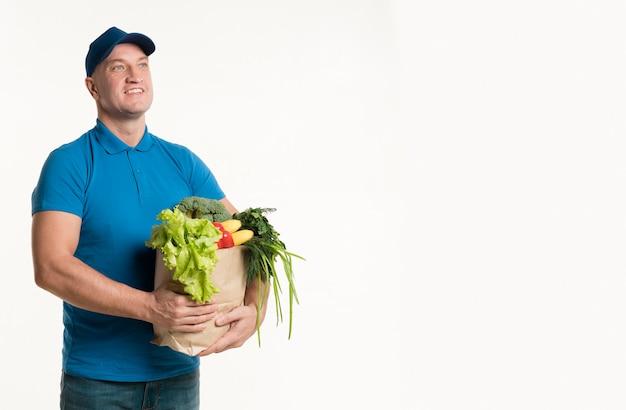 Vista frontal do entregador sorridente com sacola de compras