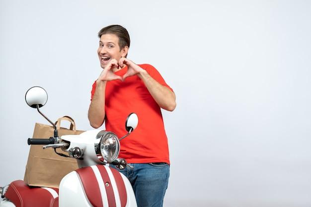 Vista frontal do entregador sorridente de uniforme vermelho em pé perto da scooter, fazendo um gesto de coração no fundo branco