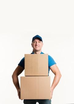 Vista frontal do entregador sorridente segurando caixas de papelão