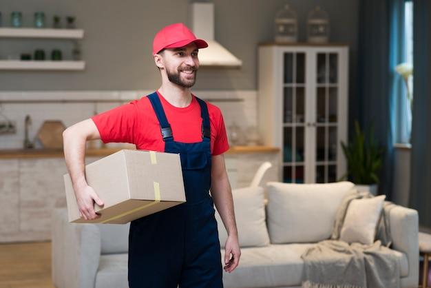 Vista frontal do entregador sorridente segurando caixas