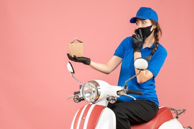 Vista frontal do entregador usando máscara médica e luvas, sentado na scooter, entregando pedidos pensando profundamente em fundo de pêssego pastel