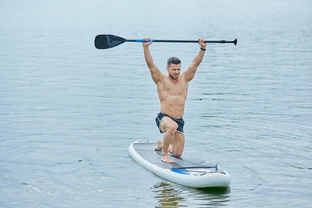 Vista frontal do esportista, mantendo o remo longo, nadando a bordo do sup no lago da cidade.