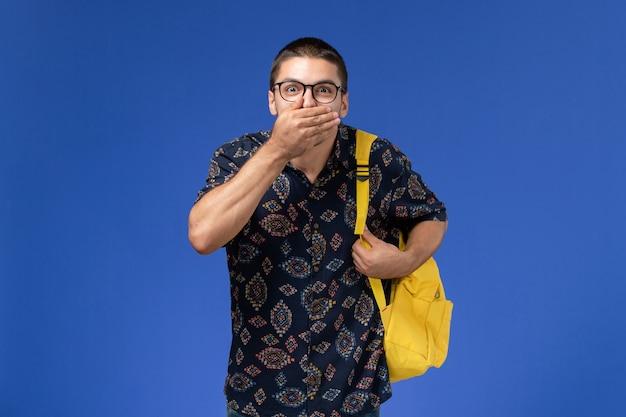 Vista frontal do estudante do sexo masculino com camisa escura e mochila amarela, fechando a boca na parede azul-clara