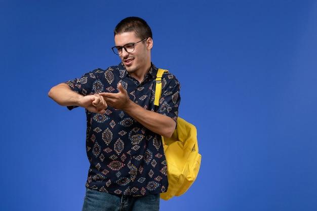 Vista frontal do estudante do sexo masculino com camisa escura e mochila amarela, olhando para o pulso na parede azul