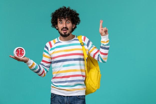 Vista frontal do estudante do sexo masculino com camisa listrada e mochila amarela segurando relógios cruzando os dedos na parede azul