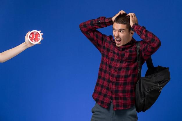 Vista frontal do estudante do sexo masculino com camisa quadriculada vermelha com mochila preta com medo de relógios na parede azul