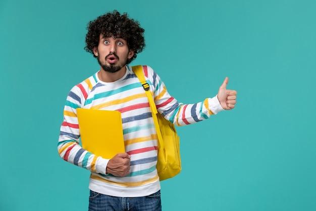Vista frontal do estudante do sexo masculino com mochila amarela segurando arquivos na parede azul