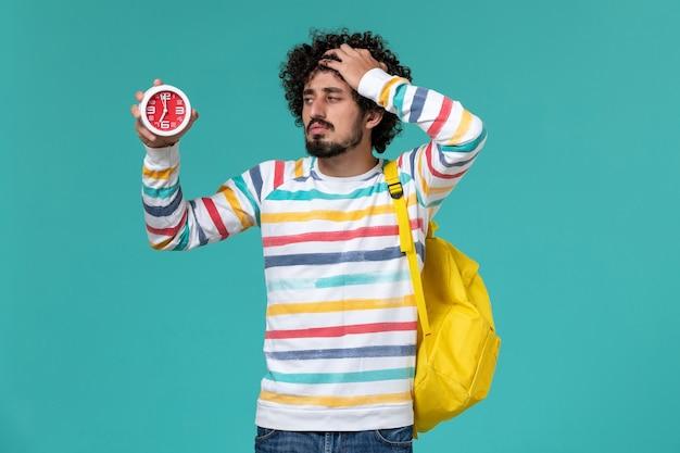 Vista frontal do estudante do sexo masculino com mochila amarela segurando o relógio na parede azul clara